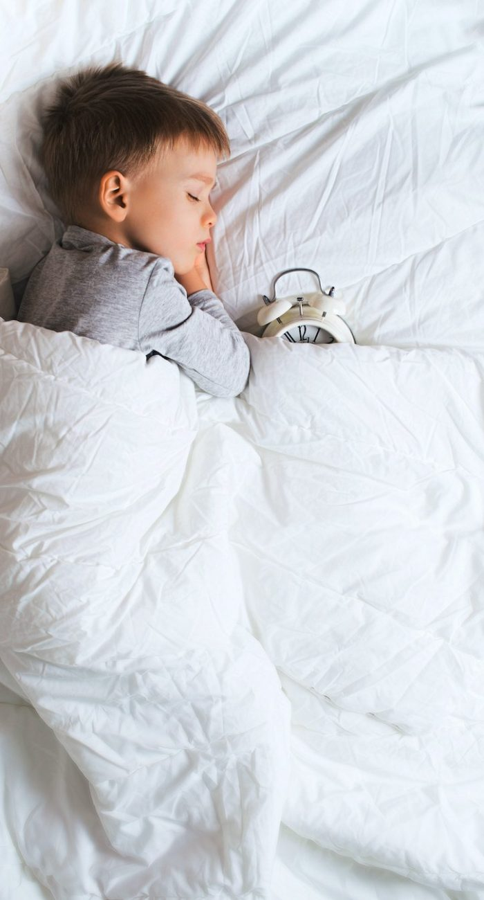 Kids sleeping concept with asleep little boy in bed with alarm clock on white background, copy space, vertical